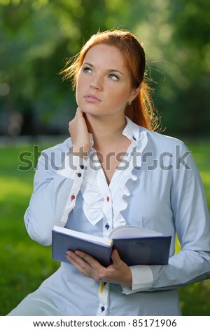 Business woman with notebook in the city garden