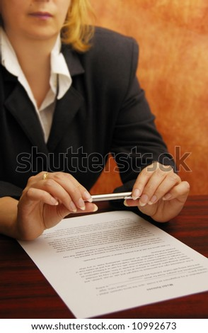 business woman with pen in hand and a contract on the desk
