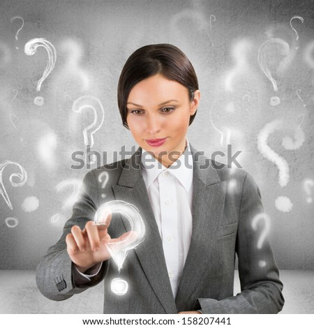 Business woman with question symbols around her. Choosing one and pressing on it - stock photo