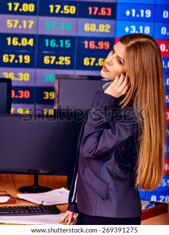 Business woman with  stock exchange board in office. - stock photo
