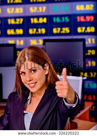 Business woman with  stock exchange board thumb up in office. - stock photo