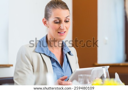 Business woman with tablet in restaurant eating lunch - stock photo