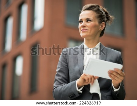 Business woman with tablet pc in front of office building - stock photo