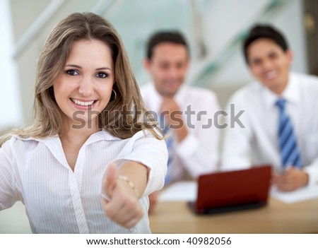 Business woman with thumbs up at the office smiling - stock photo