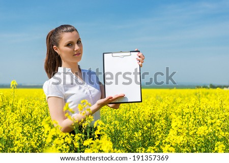 business woman with yellow flowers and blank sheet on field - stock photo