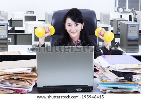 Business woman working and workout at her office - stock photo
