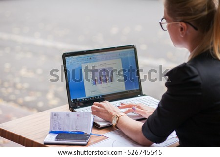 Business woman working at a laptop with documents and diagrams