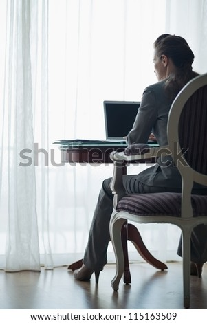 Business woman working at desk in hotel room