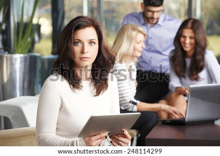 Business woman working at digital tablet while sitting at staff meeting at office.