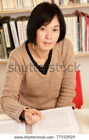 Business woman working at home sitting and looking at you, half length closeup portrait indoor. - stock photo