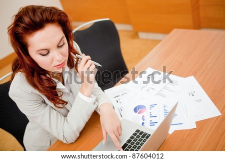 Business woman working at the office with a laptop - stock photo