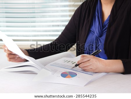 Business woman working in her office room. Person working on financial data in the form of charts. Woman is dress in business casual wear. - stock photo