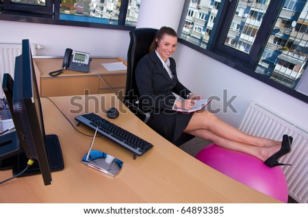business woman working in office and resting legs on pilates ball