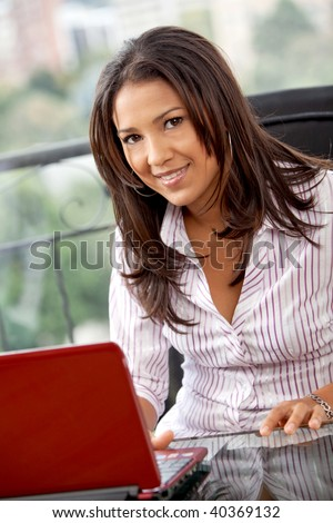 Business woman working on a laptop at an office - stock photo