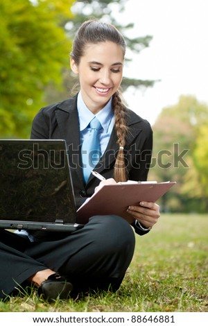 Business woman working on grass with laptop and documents - stock photo
