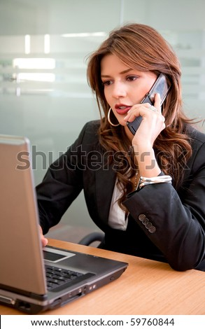 Business woman working on her laptop and talking on the phone - stock photo