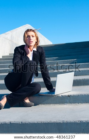 business woman working on stairs with laptop on sunny day, vertical