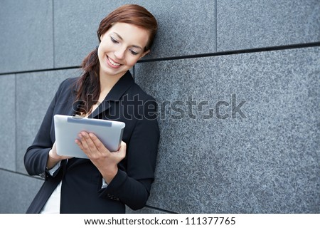 Business woman working on the way with tablet computer - stock photo