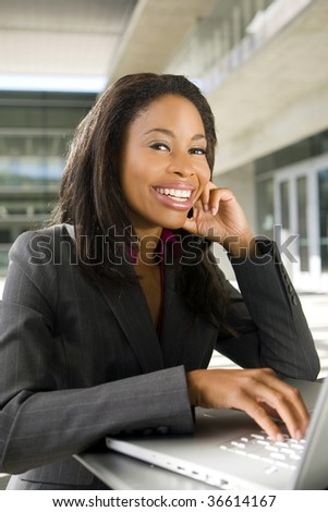 Business woman working outside on her computer - stock photo