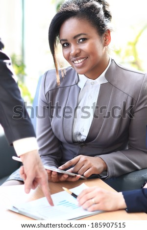Business woman working with a tablet in her hands, her co-workers discussing business matters in the background, tilt up - stock photo
