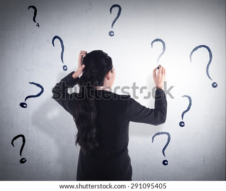 Business woman write question mark on the wall. She dont know what to write - stock photo