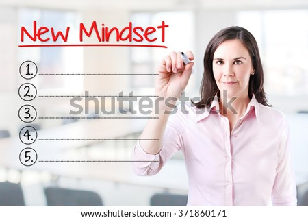 Business woman writing blank New Mindset list. Office background.  - stock photo