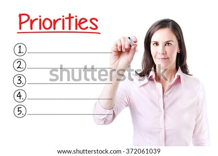 Business woman writing blank Priorities list. Isolated on white.  - stock photo