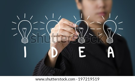 Business Woman writing IDEA Light Bulb concept - stock photo