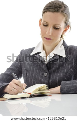 Business woman writing in her notepad on white office desk. Focus on a pen.