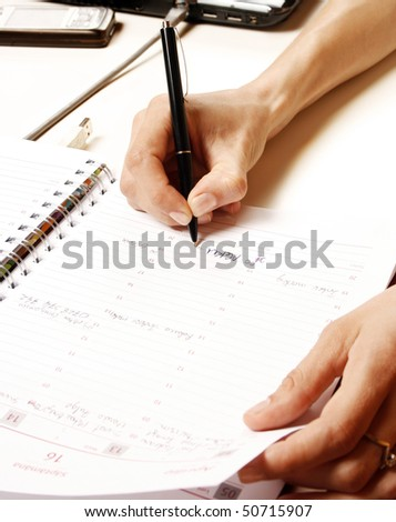 Business woman writing into notebook