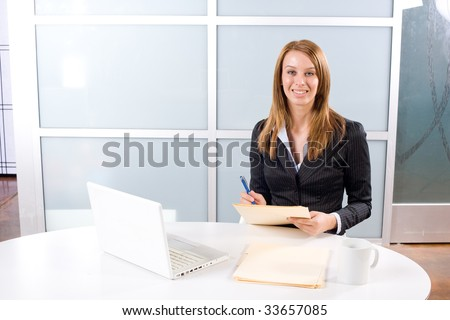 Business Woman Writing notes at desk in a modern office - stock photo