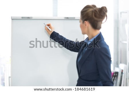 Business woman writing on flipchart