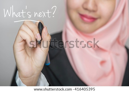 Business woman writing text : What's Next? over gray background - stock photo