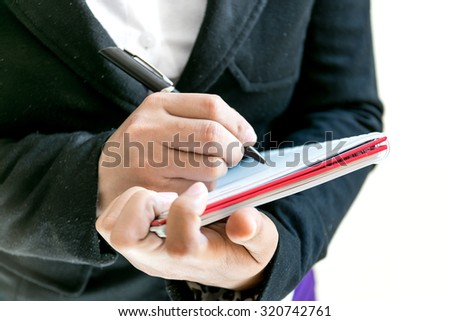 Business woman  writing the word on a notebook.