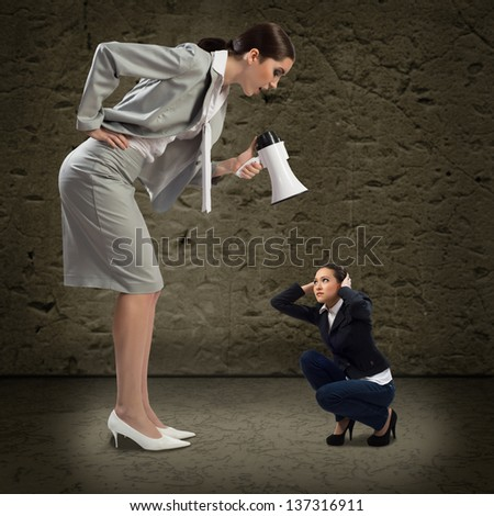 Business woman yelling at a small woman sitting on the ground, the concept of aggression