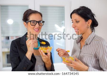 business women eating fruits salad - stock photo