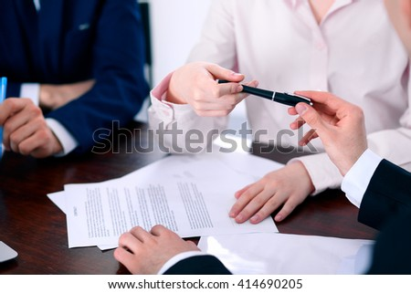 Business women giving a pen to business man for contract signing