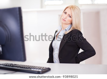 Business women having back pain at computer workplace - stock photo