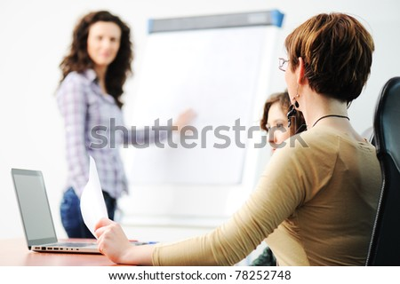 Business women holding a conference writing on an a board in an office - stock photo