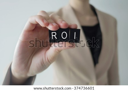 Business women holding ROI letter against a defocussed background with cool image temperature as an Investment Concept - stock photo