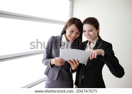 Business women look and smile conversation with Digital Tablet in Office, asian - stock photo