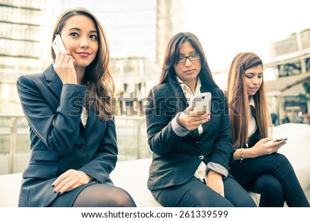 Business women of different ethnics talking and texting with mobile phone - Women sitting outdoors - Business,technology,multiracial concepts - stock photo