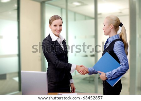 Business women shaking hands over meeting in office