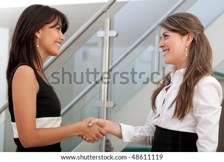 Business women smiling and doing a handshake - stock photo