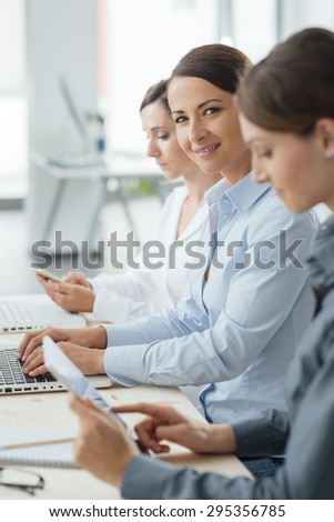 Business women team working at office desk using laptops and mobile devices