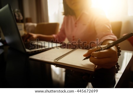 Business women using laptop and note some data on notepad - stock photo