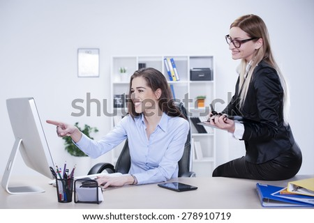 Business womens in office looking at computer monitor - stock photo