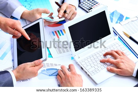 Business work-group analyzing financial data in office - stock photo