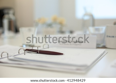 Business work place with pen and papers on the table - stock photo