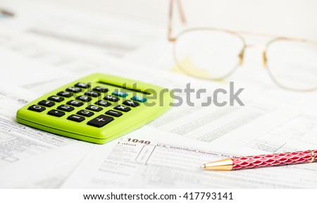 Business work station with paperwork income tax return, calculator and pen - stock photo